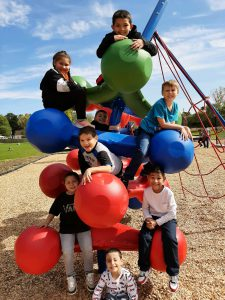 kids climbing on playground equipment that looks like giant balls.