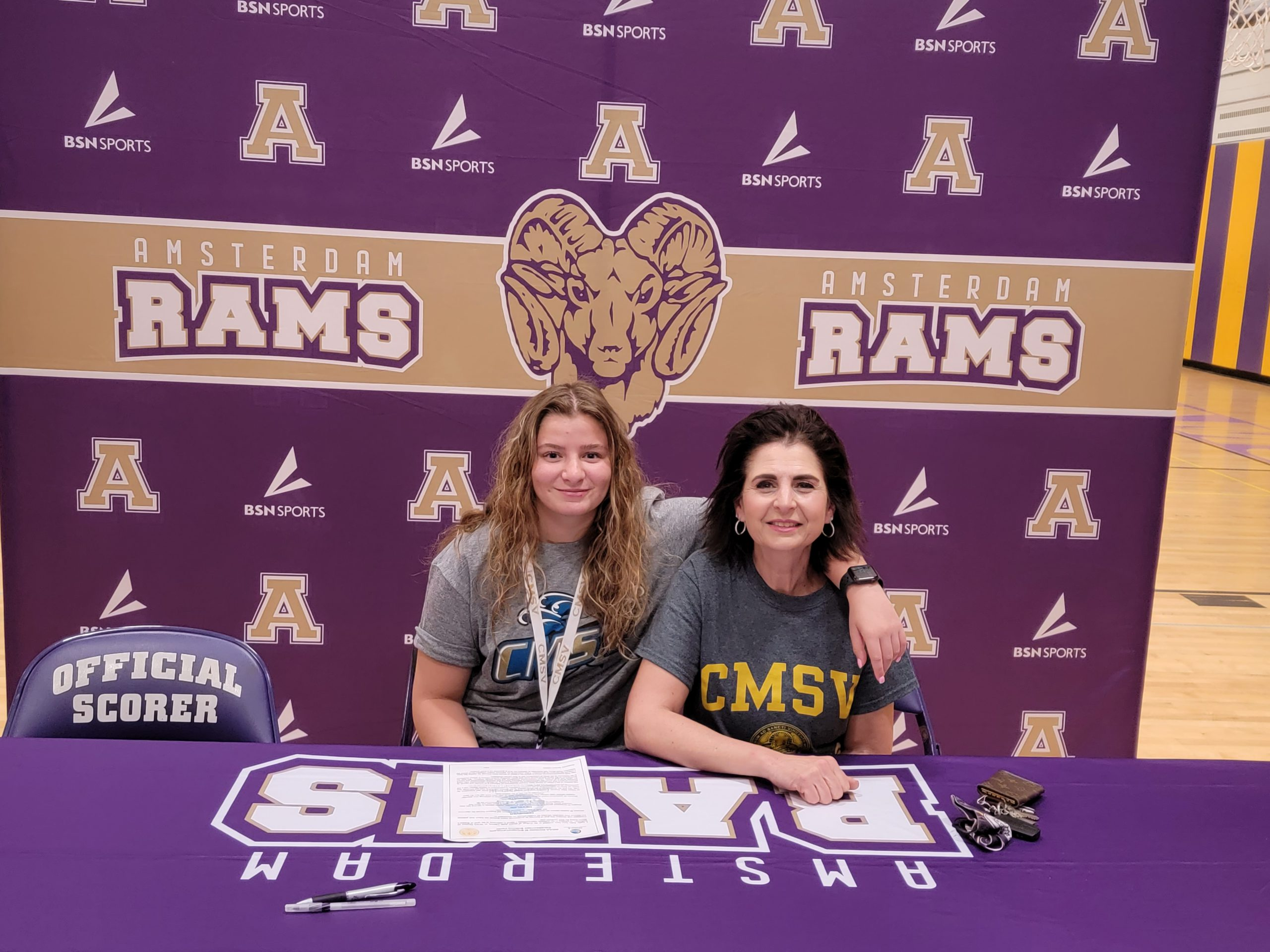female athlete and mom sit together at a table with the Rams banner behind them