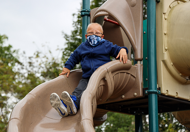 boys about to slide down a playground slide wearing a mask