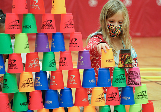 girl wearing mask stacking large, colorful cups