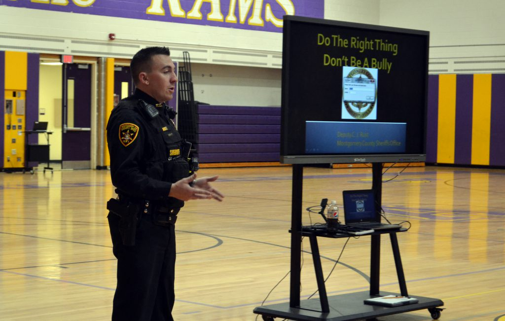 SRO Corey Rust stands beside a TV screen that has a bullying presentation on it.