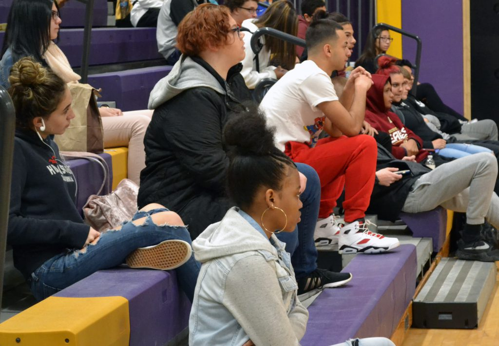Students sit in the bleachers watching a presentation.