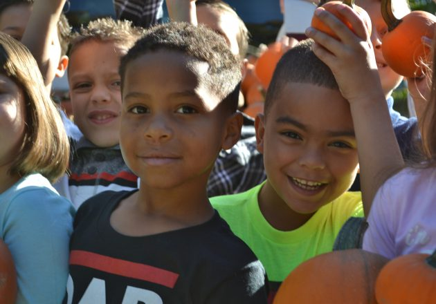 Students smile holding pumpkins outside.