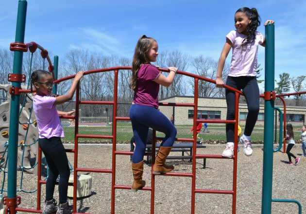 Students climb the playground outside.