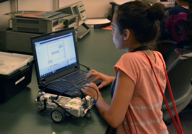 A student uses a laptop to code while a robotic device sits beside them.