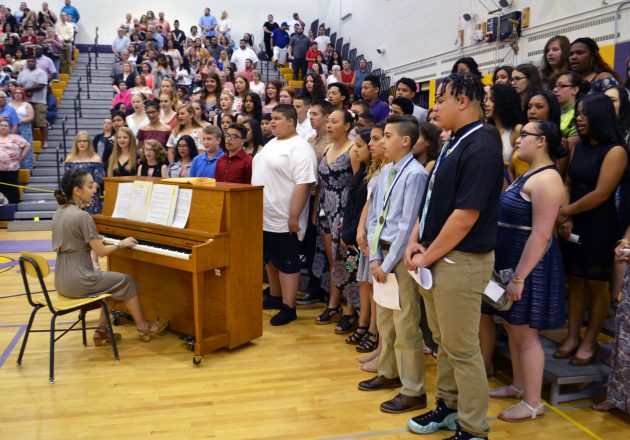 Students gather around a piano at the Moving Up Ceremony.
