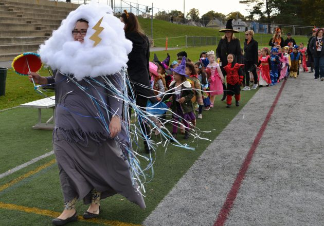 A teacher dressed as a thunderstorm leads a Harvest Festival parade outside.