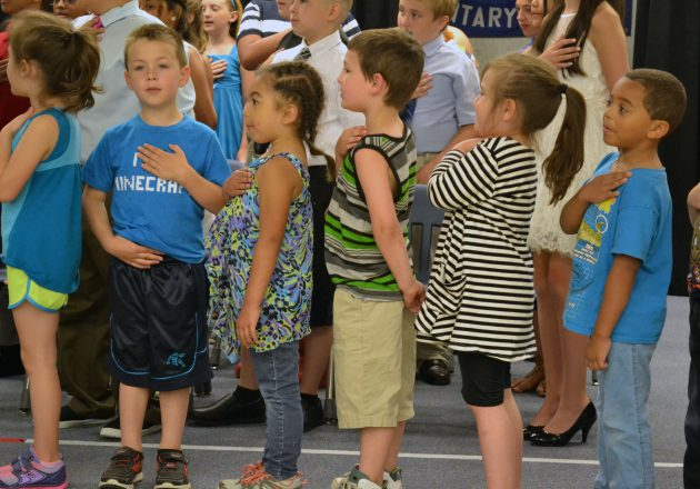 Students place their hands over their hearts during an assembly.