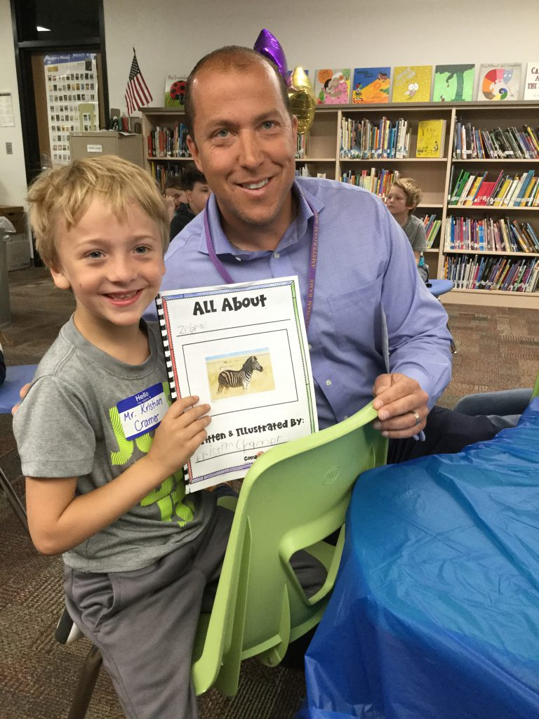 student shares book with adult
