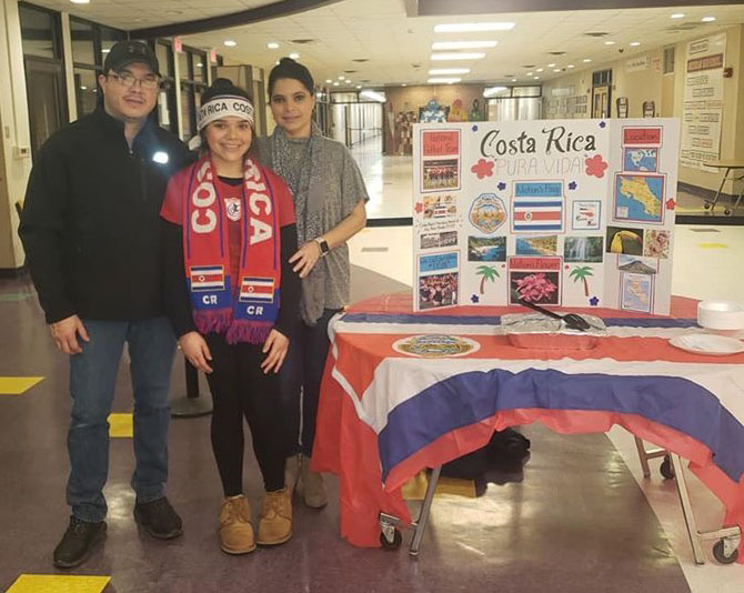 family from costa rica stands in front of table display