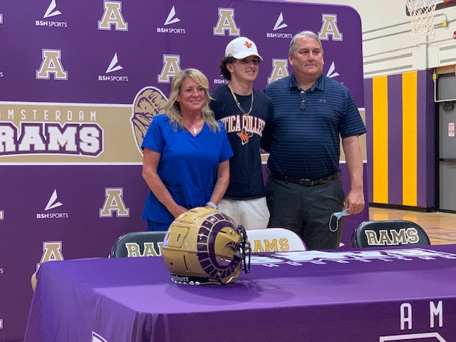 athletic in hat stands with his parents