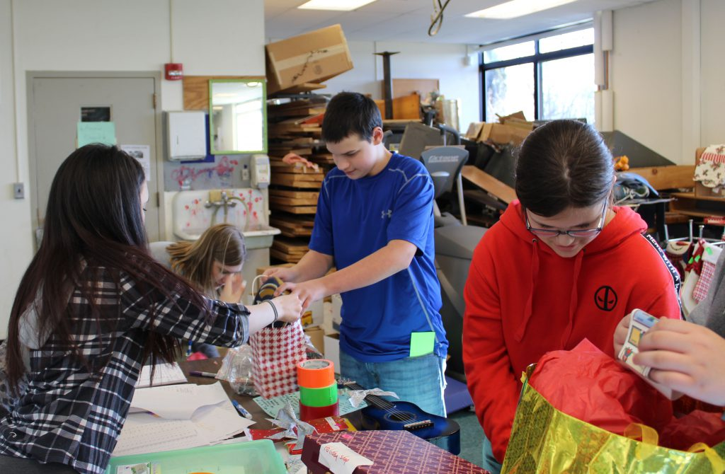 Students use stamps to get gifts at the school's Holiday Shop.