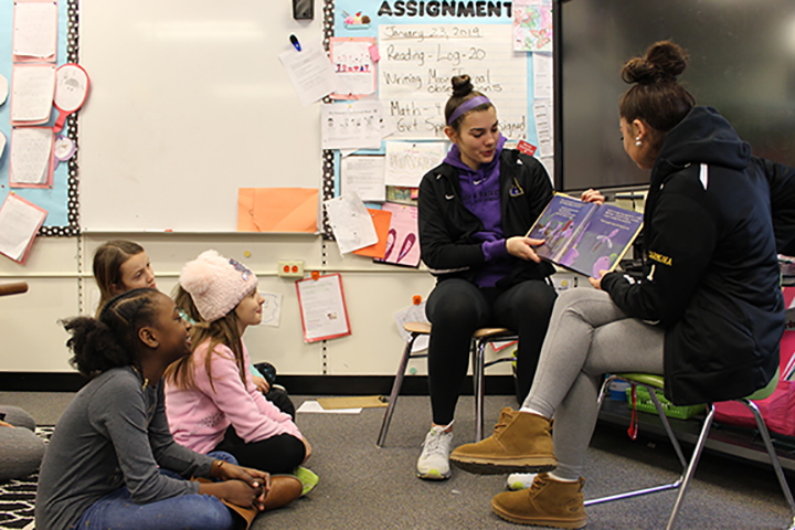 Two high school students reading to younger students.