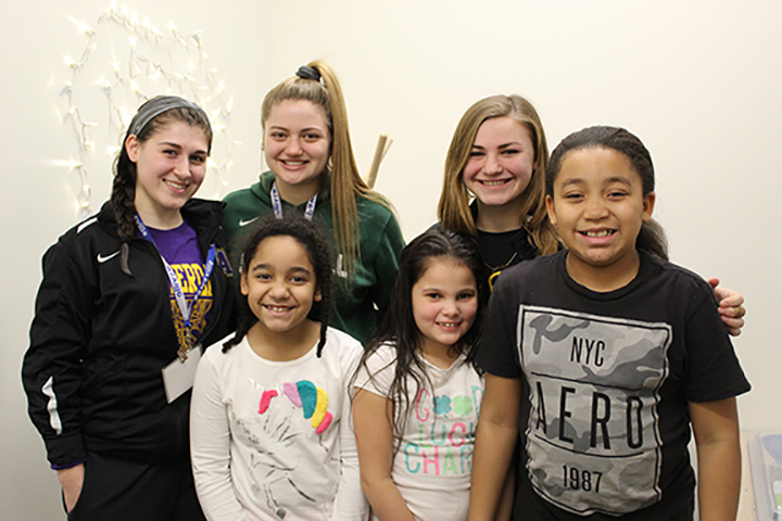 Three high school students standing with three elementary students.