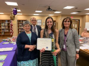 teacher holds award and flower, stands with three other people