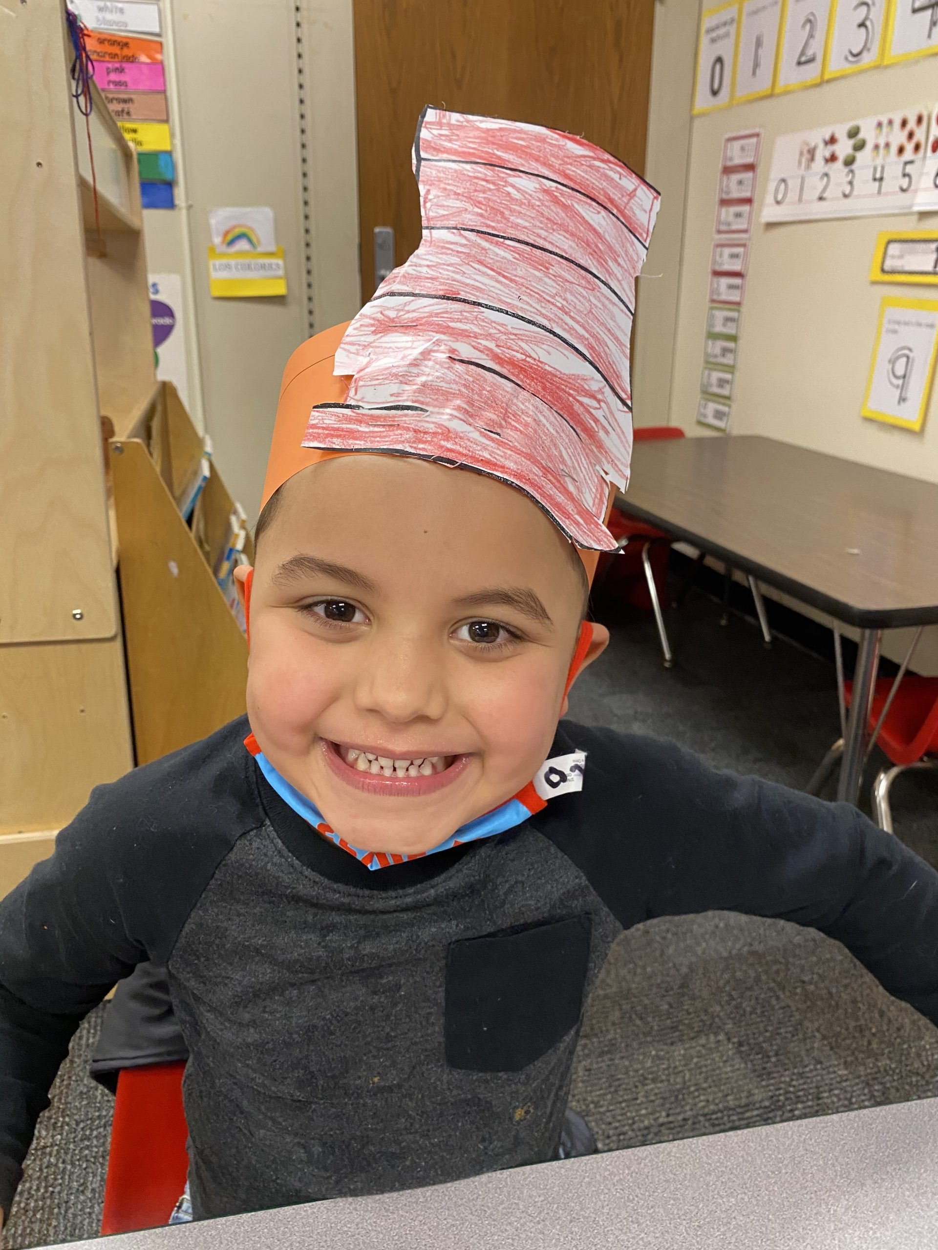 smiling young boy wearing a handmade Dr. Suess hat