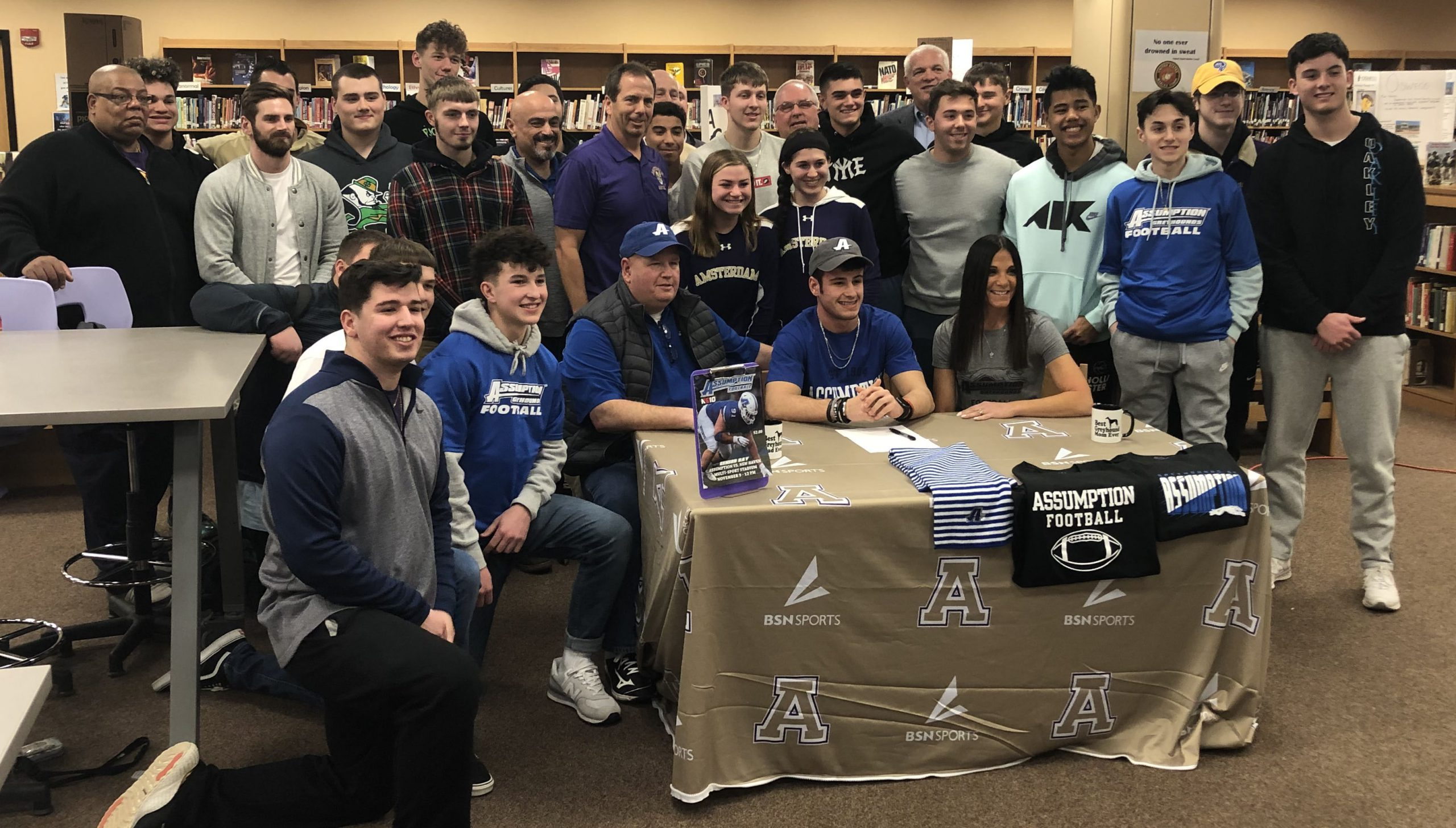 football team surrounds his teammate signing letter of intent at table