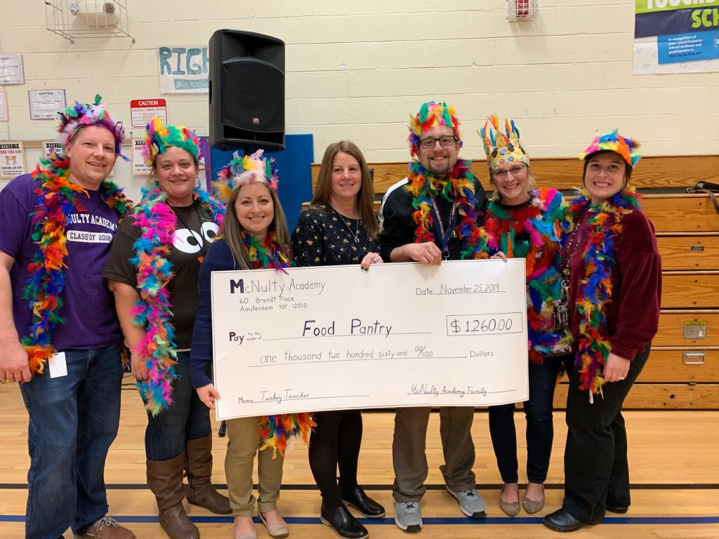 Teachers dressed up with feather boas and feather hats stand with executive director of local charity holding a large mock donation check.