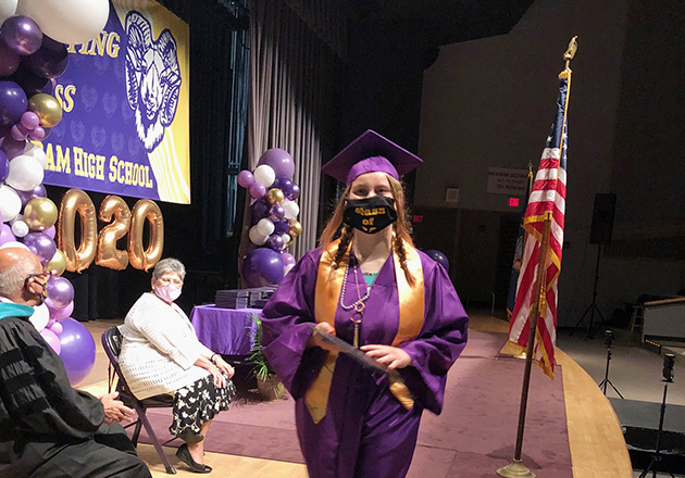 girl walk across stage with diploma
