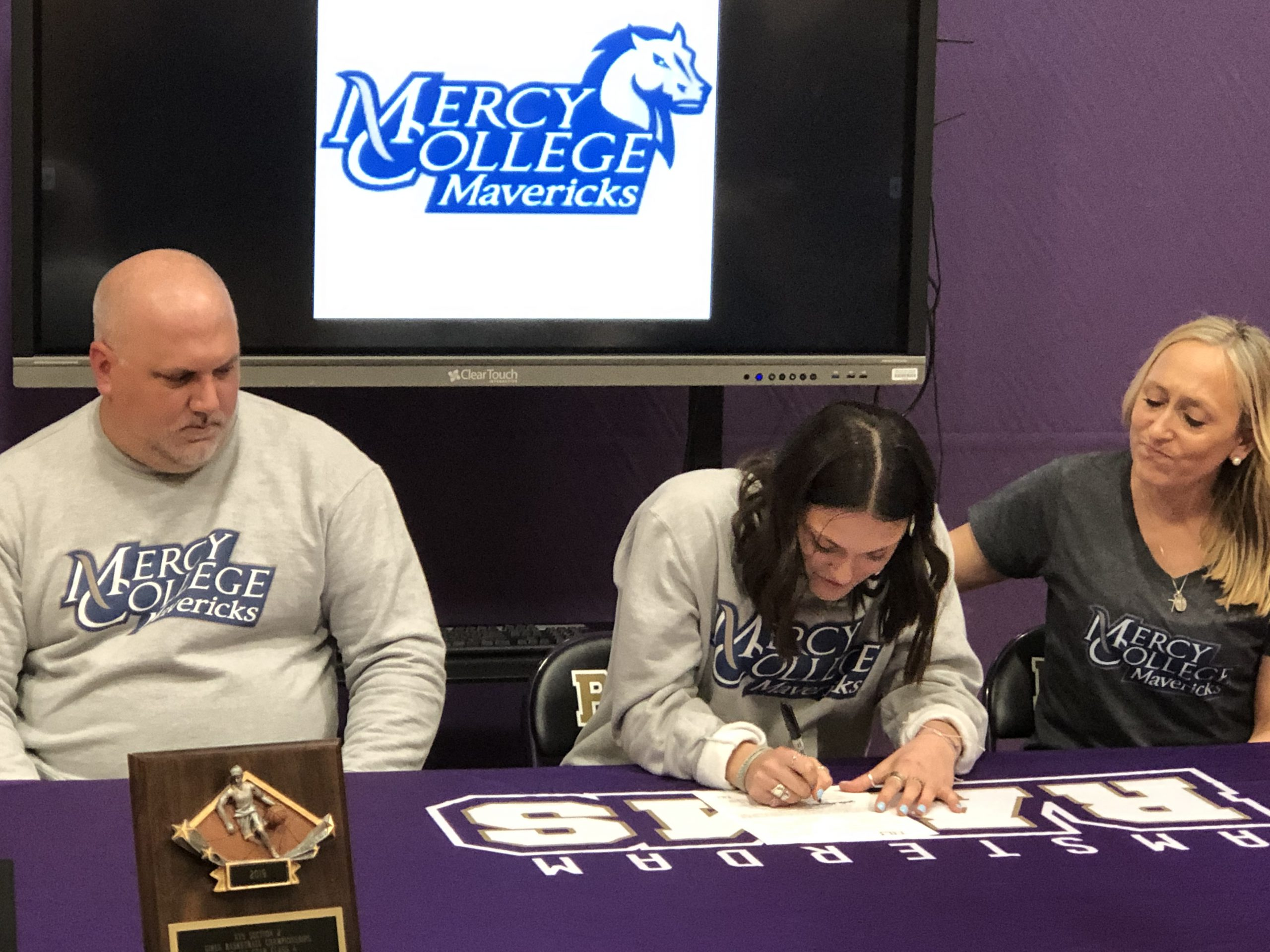 girls signs letter at table with her mom and dad