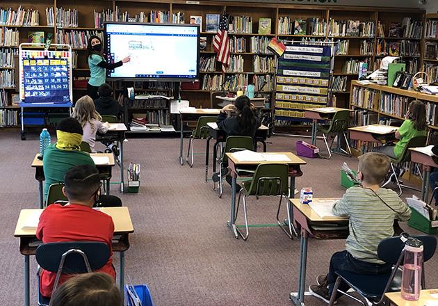 teacher teaches a class full of students