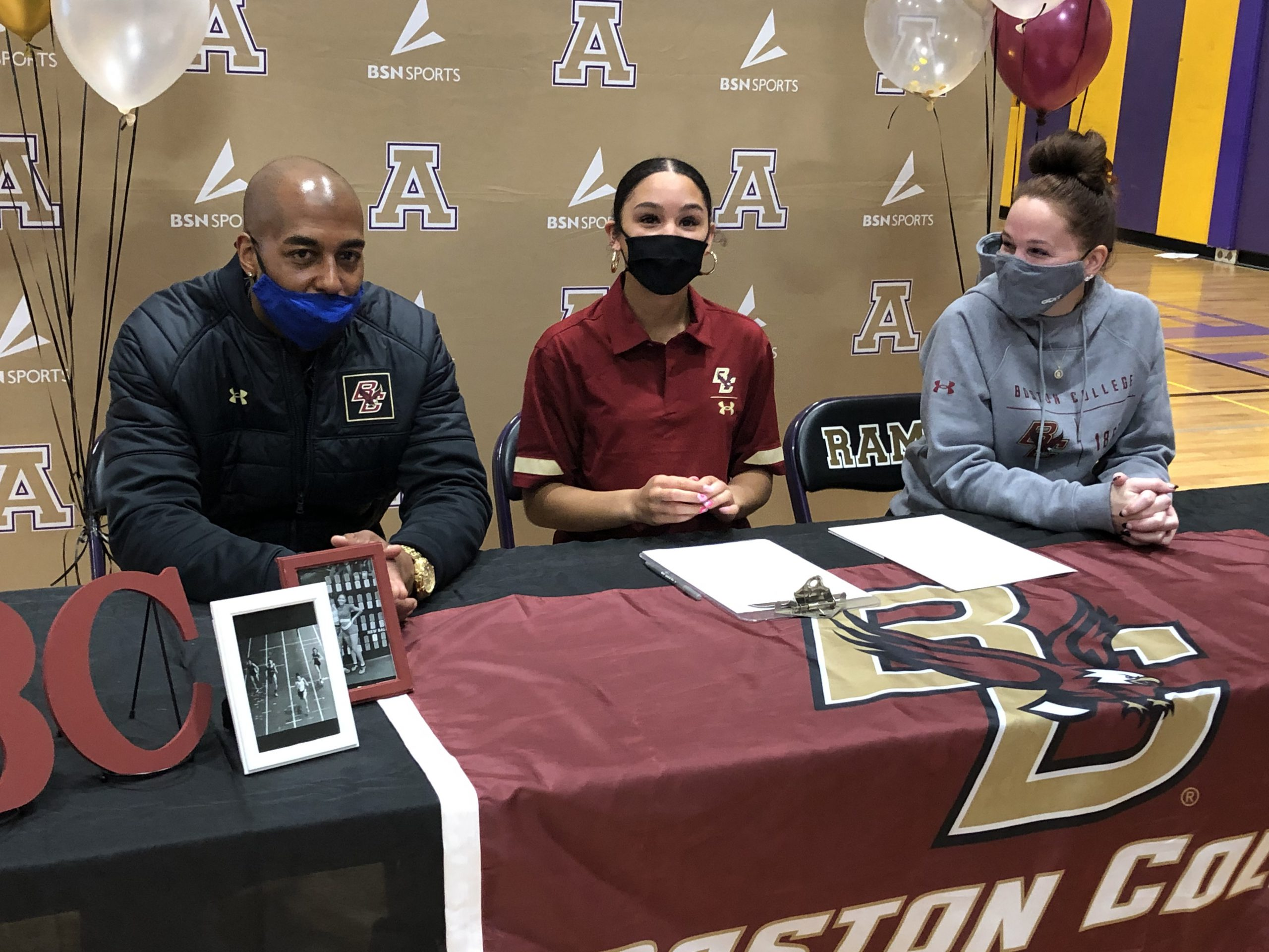 girl signs scholarship letter with her mom and dad seated beside her