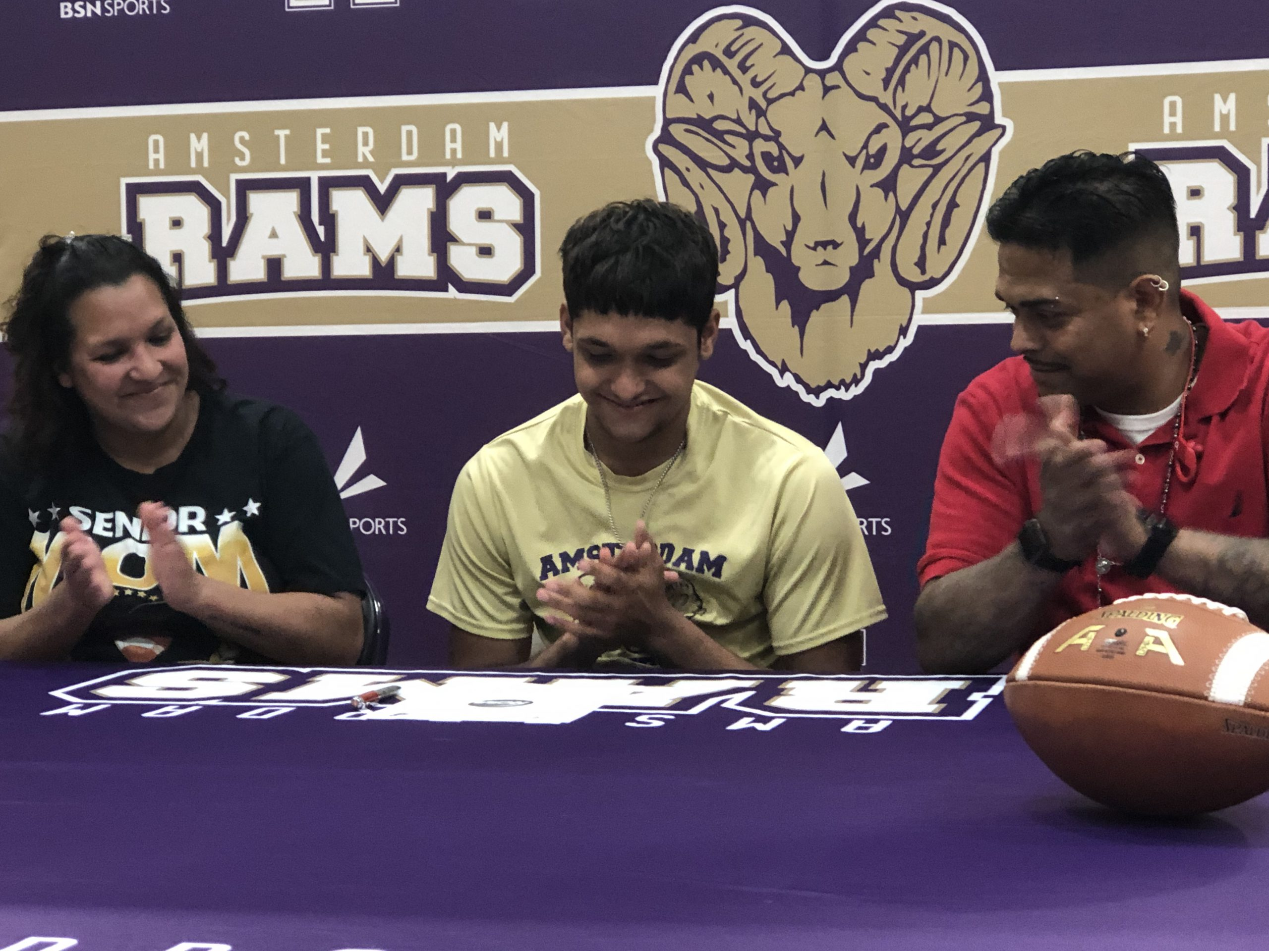 athlete at table signing letter with his parents