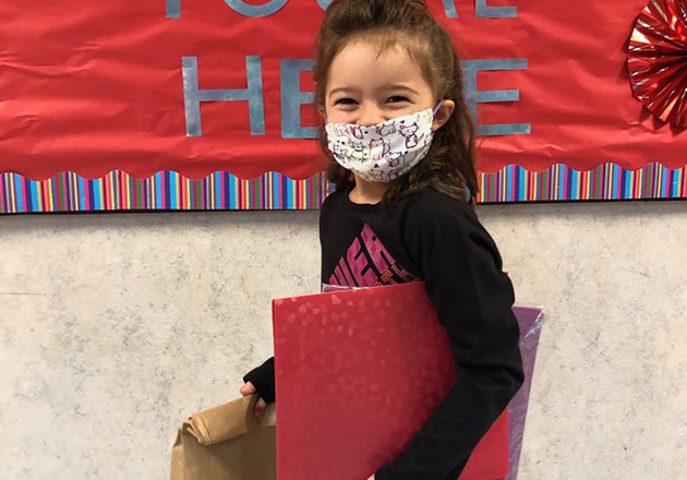 girl wearing her mask and carrying a lunch bag