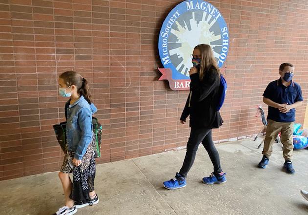 3 kids walking into school on sidewalk
