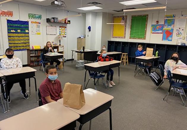 kids sitting at desks in classroom wearing masks