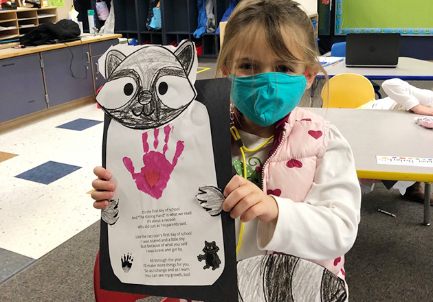 little girl wearing a mask and showing off a paper raccoon