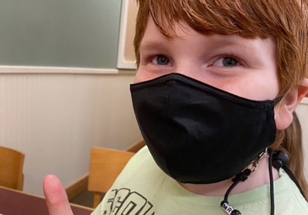 boy with mask giving thumbs up