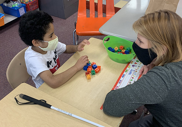 boy works with a teacher at a table, both wearing masks