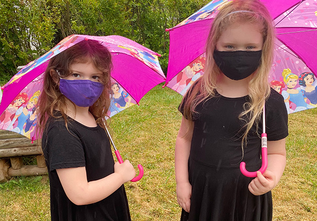 2 girls wearing masking holding purple umbrellas