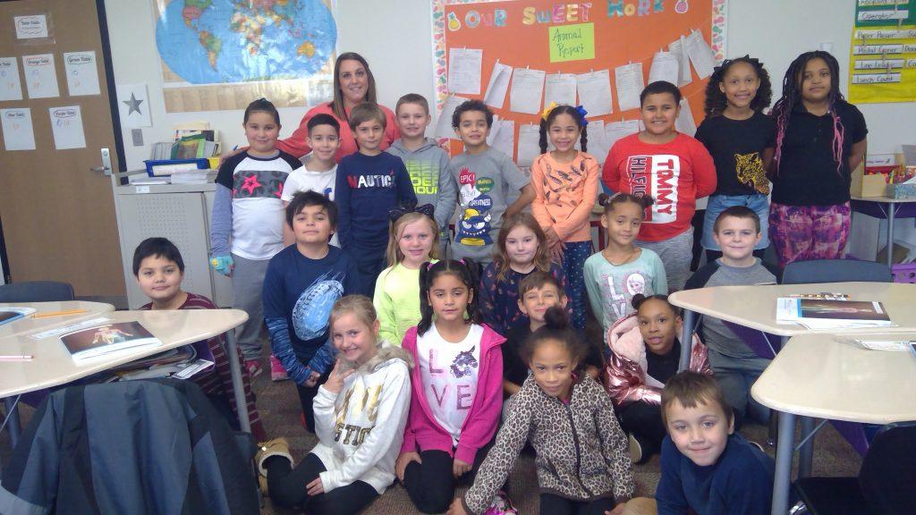 class photo of a third grade class in their classroom with their teacher