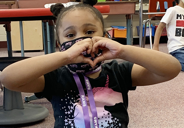 Afro American girl sitting on floor making heart symbol with her hands wearing and mask