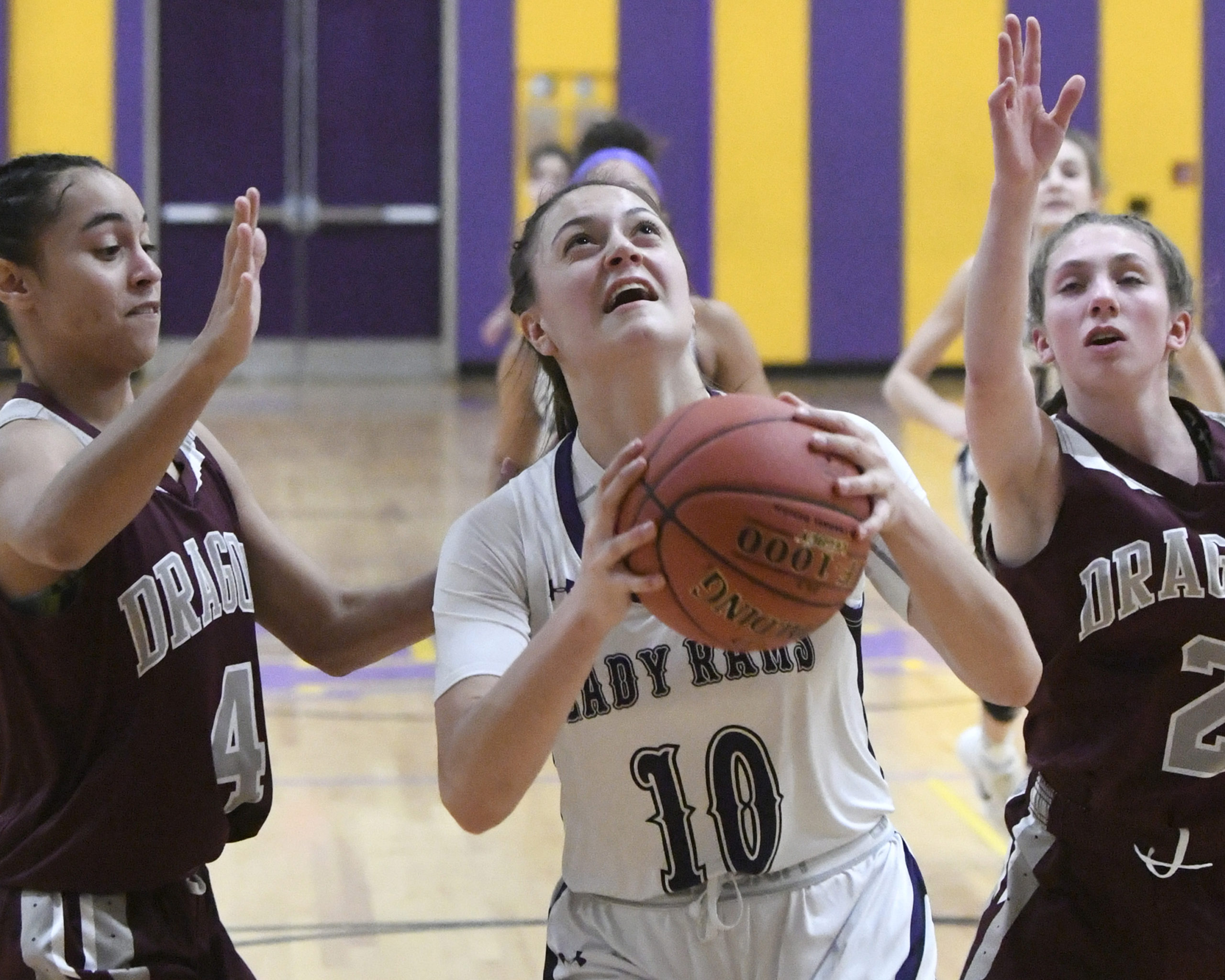 girl holds basketball defended by 2 other players