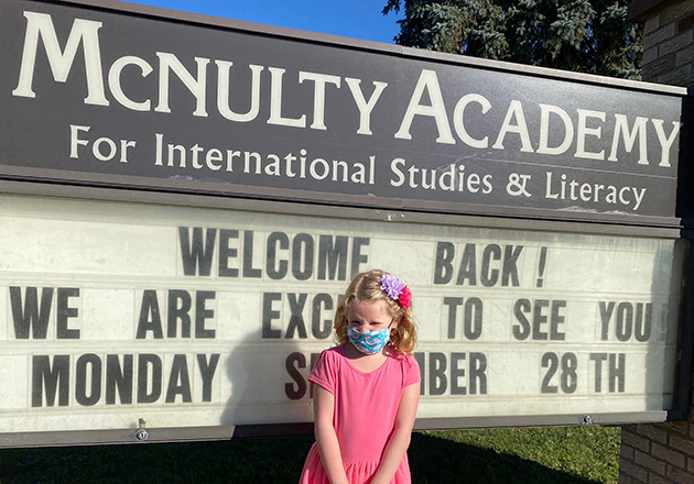 girl in front of mcnulty school sign