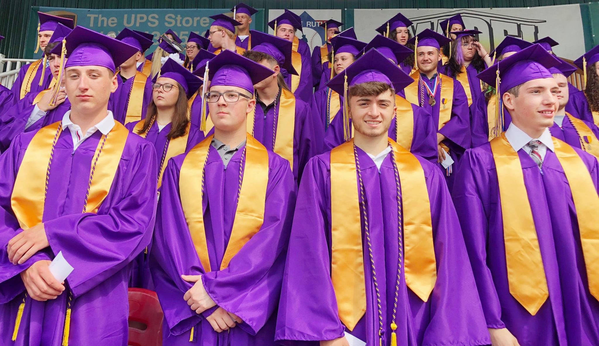 four male graduates in their caps and gowns