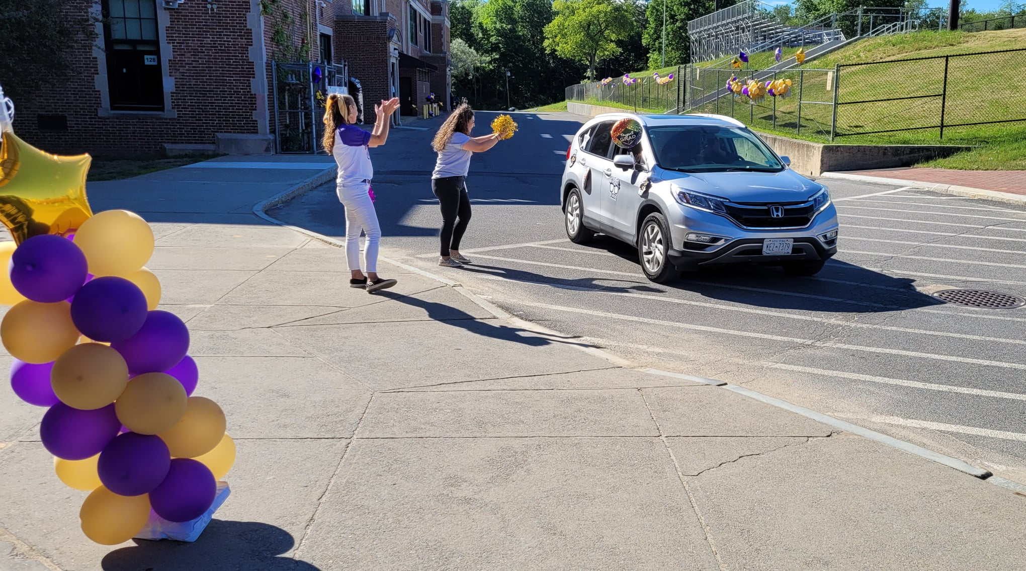 two cheerleaders cheer a car going by