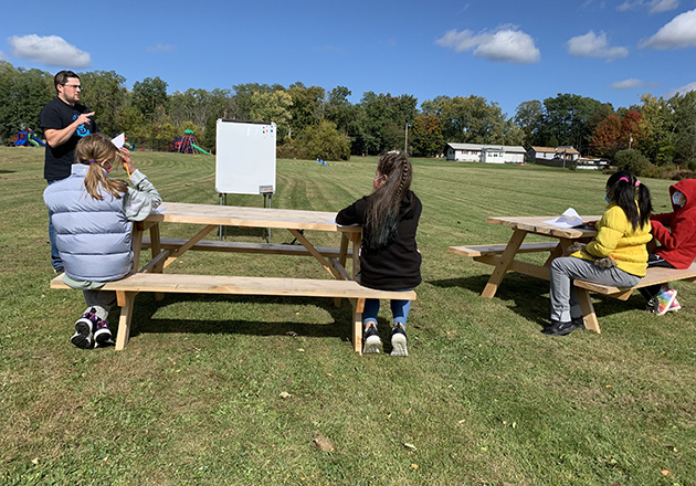 students sit at picnic tables will teacher instructs outside on a lawn